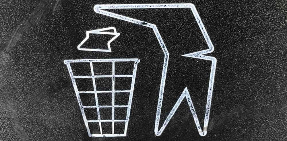 Une forme humaine jetant un papier dans une poubelle.